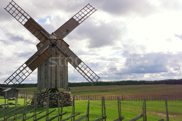 Wooden windmill against cloudy sky. Stock photo © Nejron