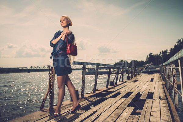 Stylish beautiful blond woman with white scarf and red bag standing near rails of old pier Stock photo © Nejron