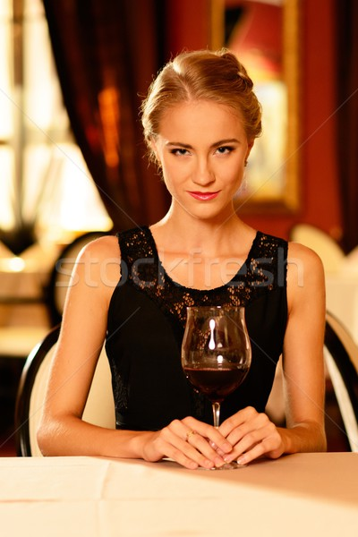 988fe9ee3 Stock photo: Beautiful young girl with glass of red wine alone in a  restaurant