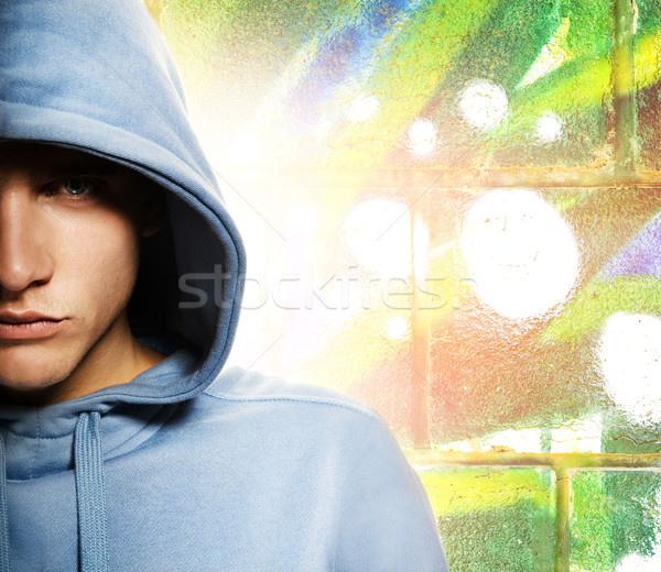 Cool looking man in a hood over abstract graffity background Stock photo © Nejron