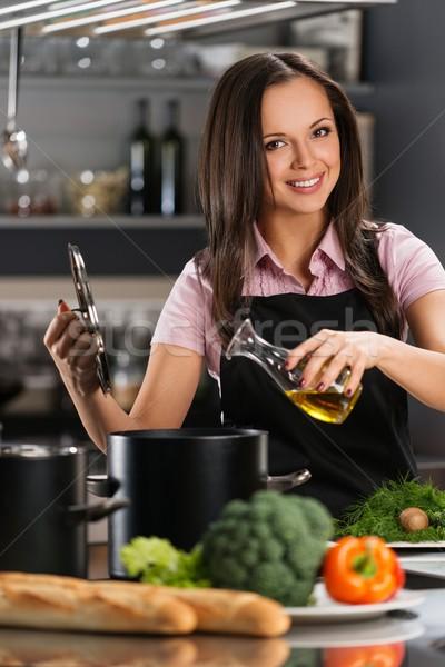 Smiling young woman adding oil to pot on a modern kitchen  Stock photo © Nejron