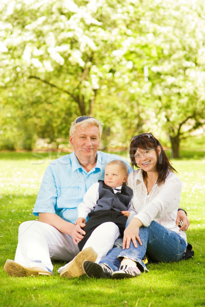 Happy family sitting on a meadow in park Stock photo © Nejron