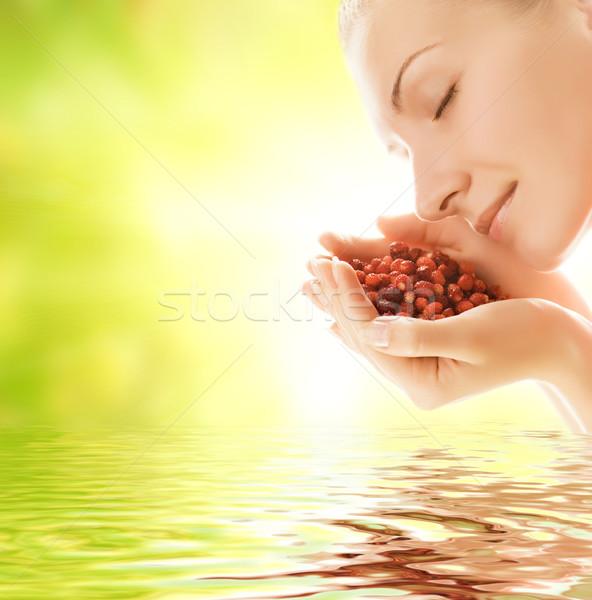 Beautiful young woman holding handful of fresh strawberries refl Stock photo © Nejron