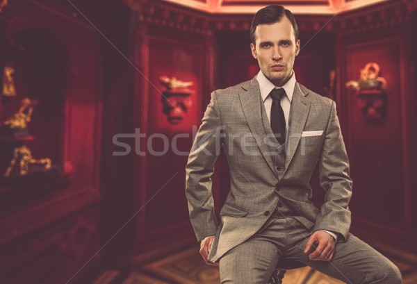 Confident man in classic grey suit sitting on chair in cabinet Stock photo © Nejron