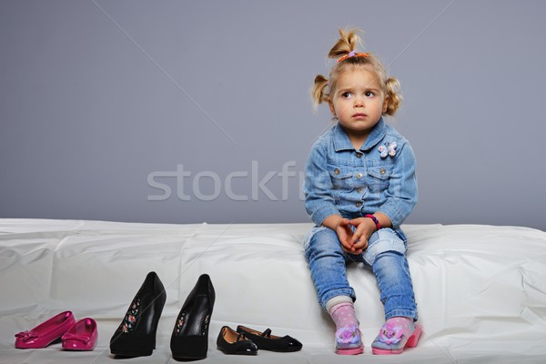 Disappointed little girl sitting on a bed with different shoes near  Stock photo © Nejron