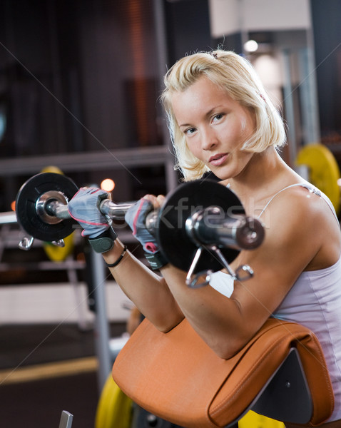 Strong beautiful woman lifting heavy weights Stock photo © Nejron