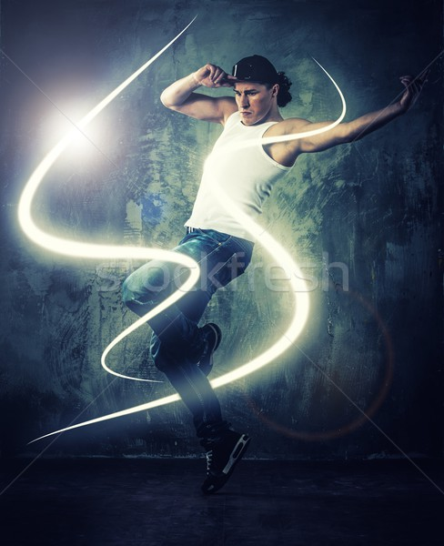 Stylish man dancer showing break-dancing moves with magic beams around him  Stock photo © Nejron