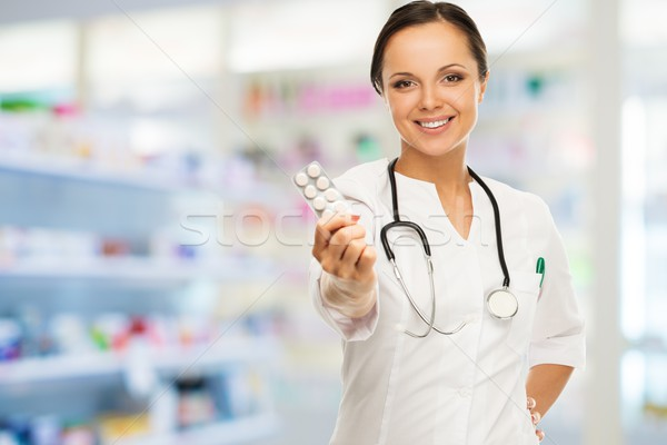 Young positive brunette doctor woman holding pills in drug store  Stock photo © Nejron