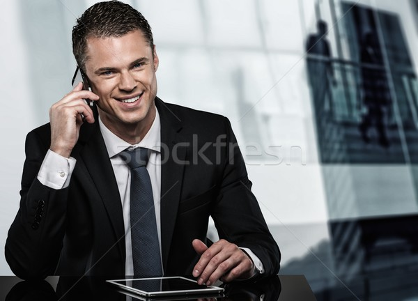 Handsome man in black suit with mobile phone and tablet pc in modern office  Stock photo © Nejron