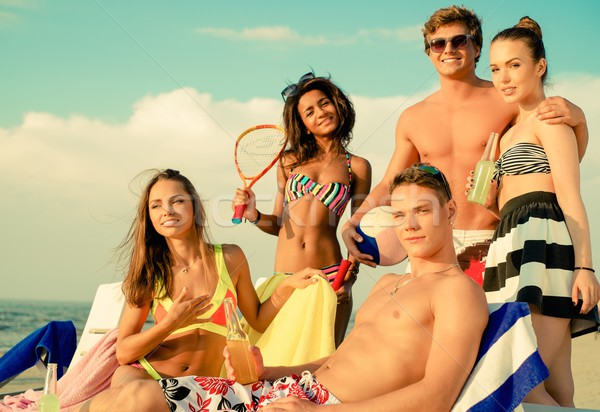 Stock photo: Group of multi ethnic friends with drinks relaxing on a beach
