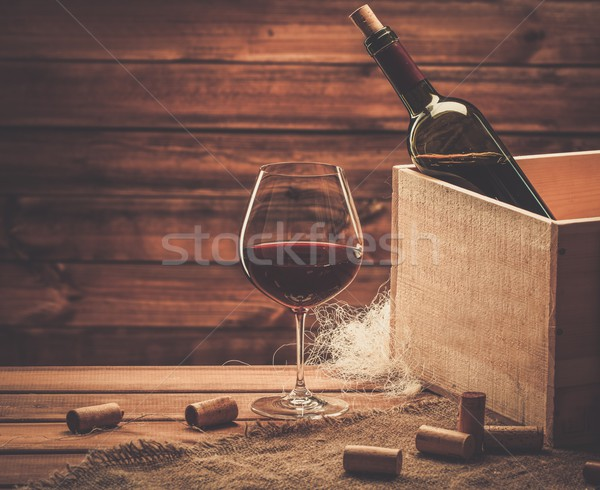 Stock photo: Bottle and glass of red wine on a wooden table