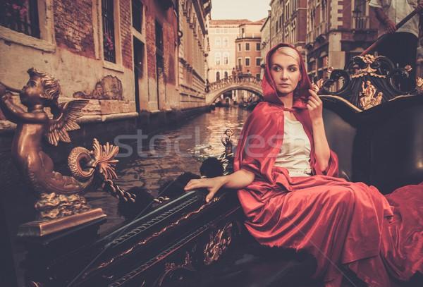Gyönyörű nő piros köpeny lovaglás gondola víz Stock fotó © Nejron
