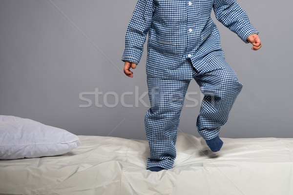 Playful little boy wearing blue pyjamas in bed Stock photo © Nejron