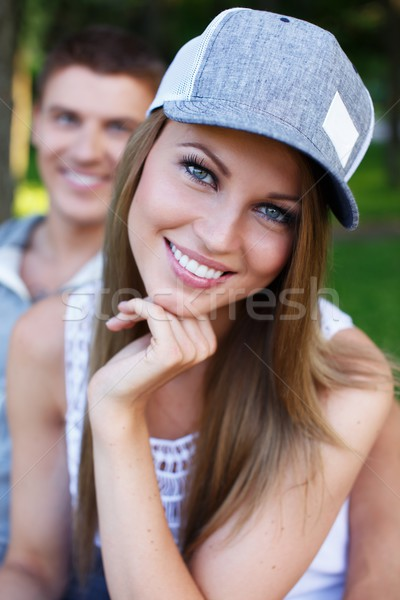 Young happy smiling sporty couple sitting on bench in a park Stock photo © Nejron