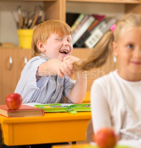 Little redhead schoolboy holding girl's plait during lesson  Stock photo © Nejron