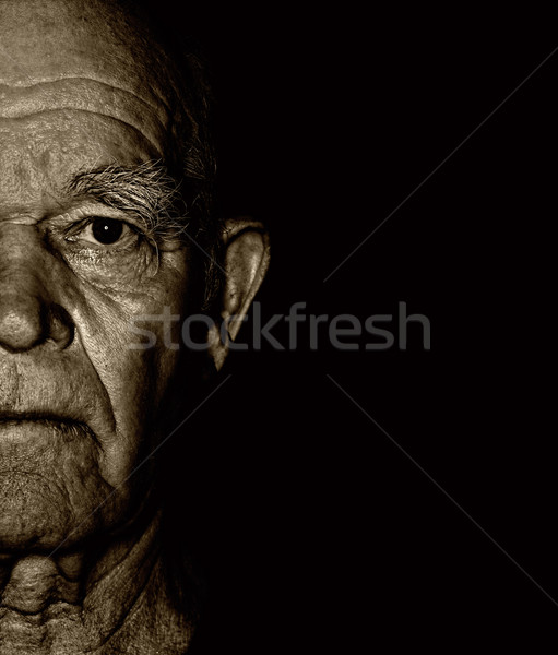 Elderly man's face over blask background Stock photo © Nejron