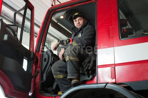 Fireman behind steering wheel of a firefighting truck  Stock photo © Nejron