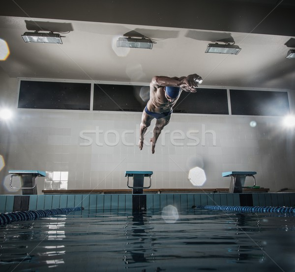 Young muscular swimmer jumping from starting block in a swimming pool Stock photo © Nejron