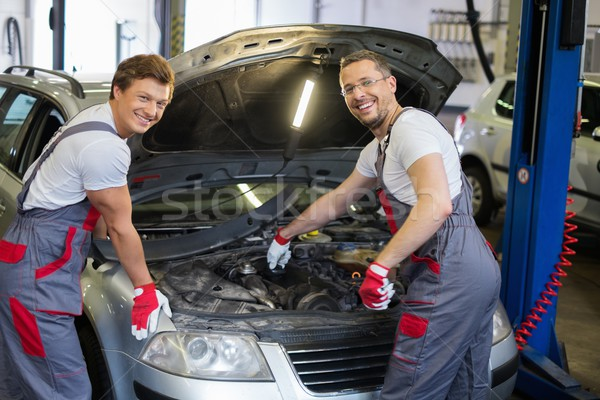 Two cheerful mechanic fixing car in a workshop Stock photo © Nejron