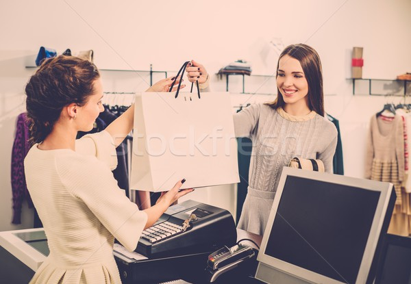 Happy customer with shopping bag in fashion showroom  Stock photo © Nejron