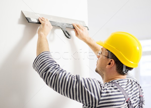 Builder levelling wall with spatula Stock photo © Nejron
