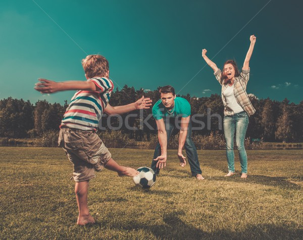 Happy young family playing football outdoors  Stock photo © Nejron