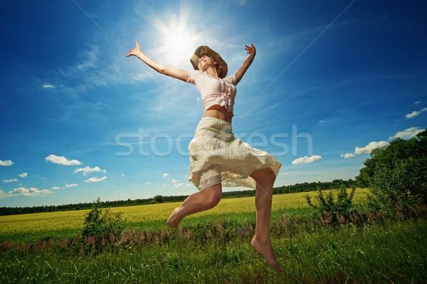 Bella donna cappello da cowboy jumping fiore sorriso erba Foto d'archivio © Nejron