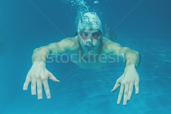 Man in swim cap and googles under water in swimming pool Stock photo © Nejron