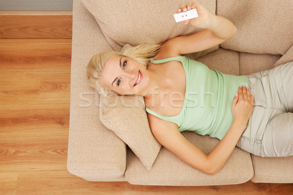 Happy young woman holding positive pregnancy test Stock photo © Nejron