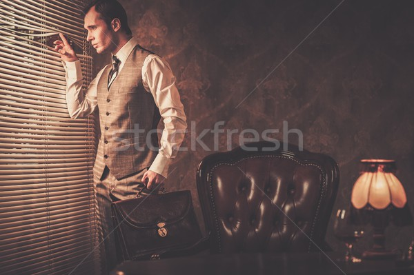 Well-dressed man with a briefcase looking through jalousie  Stock photo © Nejron