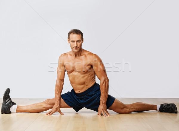 Handsome muscular man doing the splits. Stock photo © Nejron