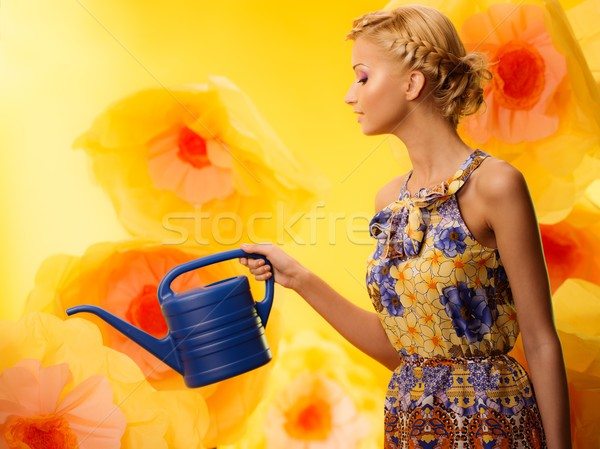 Stock photo: Beautiful young cheerful blond woman in colorful dress among big yellow flowers with watering can