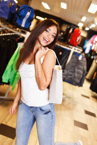 Beautiful happy brunette girl with shopping bag in a sport outlet Stock photo © Nejron