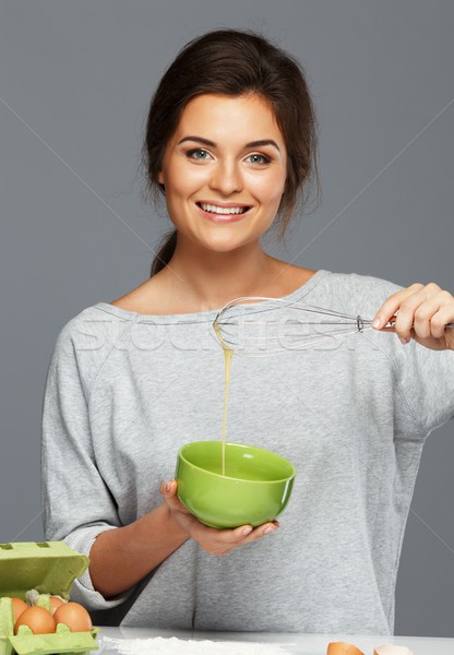 Young woman whisking eggs for a dough Stock photo © Nejron