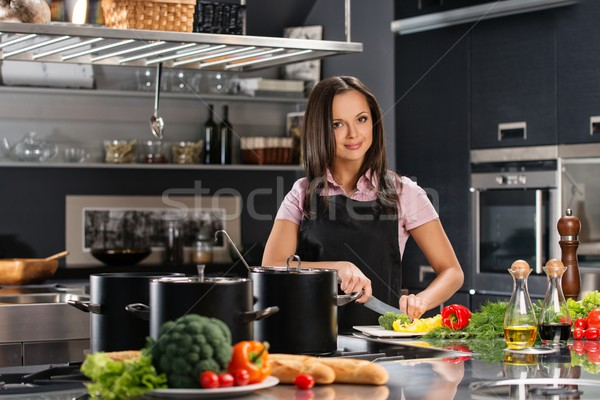 Happy young woman in apron on modern kitchen cutting vegetables Stock photo © Nejron