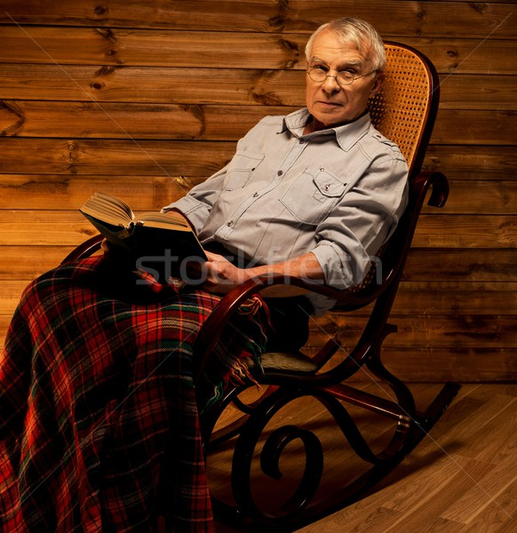 Senior man sitting in rocking chair in homely wooden interior with old book Stock photo © Nejron