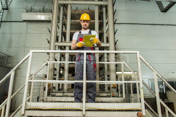 Man in a safety hat taking notes on a factory   Stock photo © Nejron