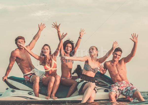 Csoport boldog többnemzetiségű barátok ül jet ski Stock fotó © Nejron