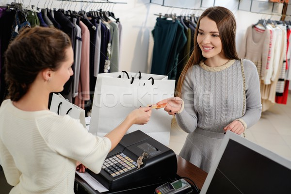 Happy woman customer paying with credit card in fashion showroom Stock photo © Nejron