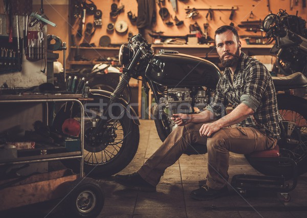 Mechanic building vintage style cafe-racer motorcycle  in custom garage Stock photo © Nejron