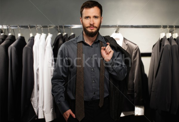 Handsome man with jacket over his shoulder in a clothing store Stock photo © Nejron