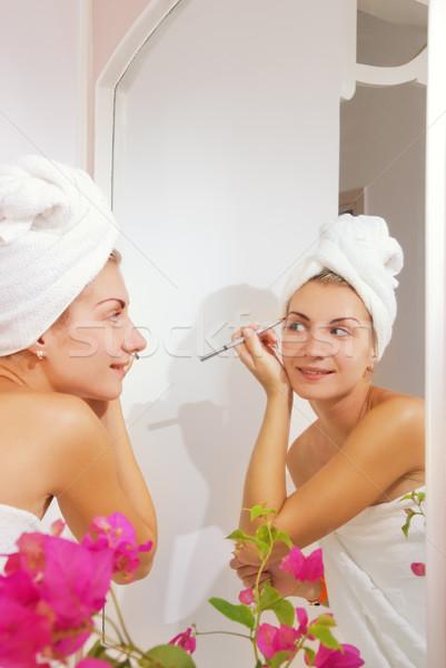 Beautiful girl applying make-up Stock photo © Nejron