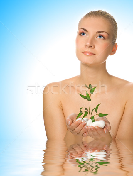 Beautiful young woman with small plant standing in water Stock photo © Nejron
