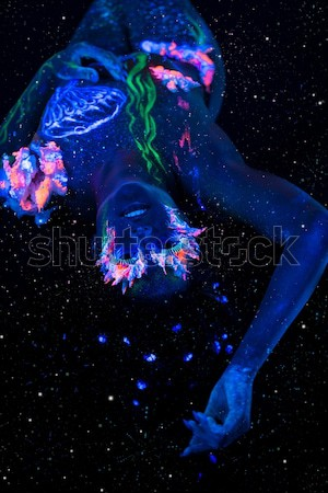 Beautiful lying woman with body art glowing in ultraviolet light Stock photo © Nejron