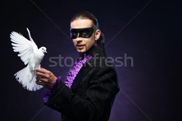Young handsome brunette magician man in stage costume with his trained white dove Stock photo © Nejron