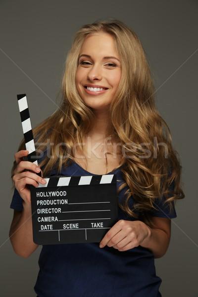 Fiatal nő hosszú haj kék szemek tart mozi tábla Stock fotó © Nejron