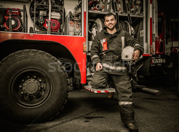 Cheerful firefighter near truck with equipment  Stock photo © Nejron