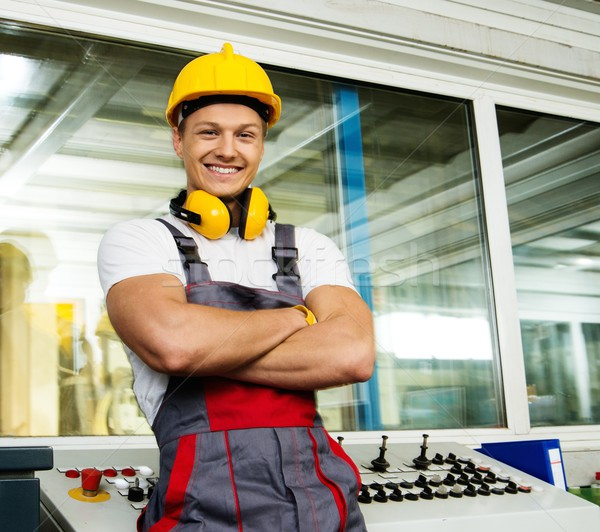 Happy worker wearing safety hat in a factory control room Stock photo © Nejron