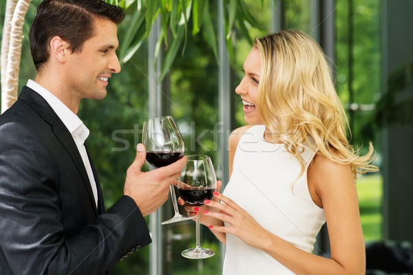 Cheerful couple with glasses of red wine talking Stock photo © Nejron
