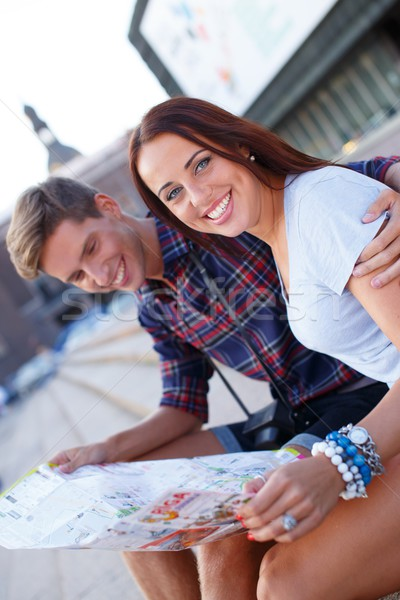 Beautiful young tourist couple with map outdoors Stock photo © Nejron